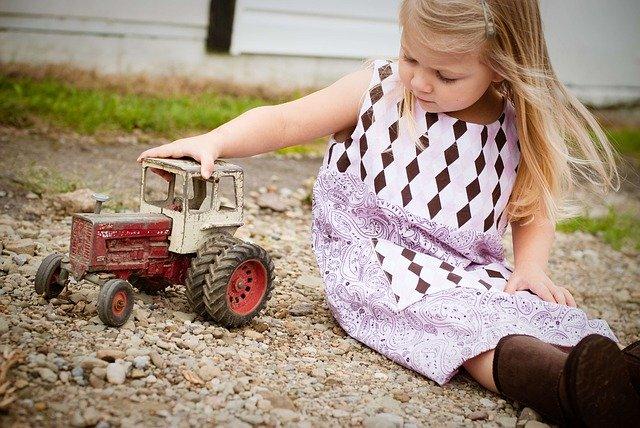 Dívka sedící na písku a hrající si s traktorem