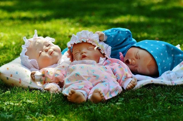 Tři panenky položené na trávě